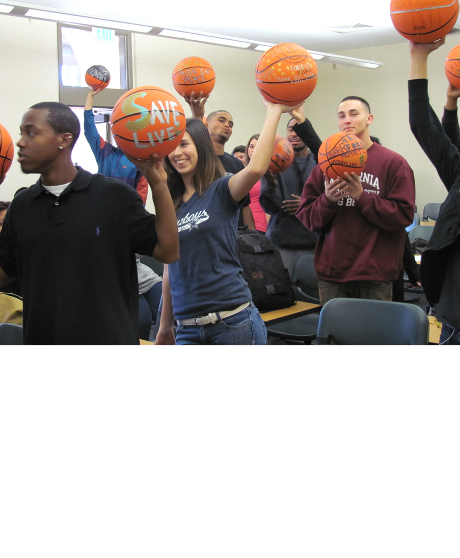 Participants in David Huffman's project Pyramid 3, showing the drawings they made on basketballs